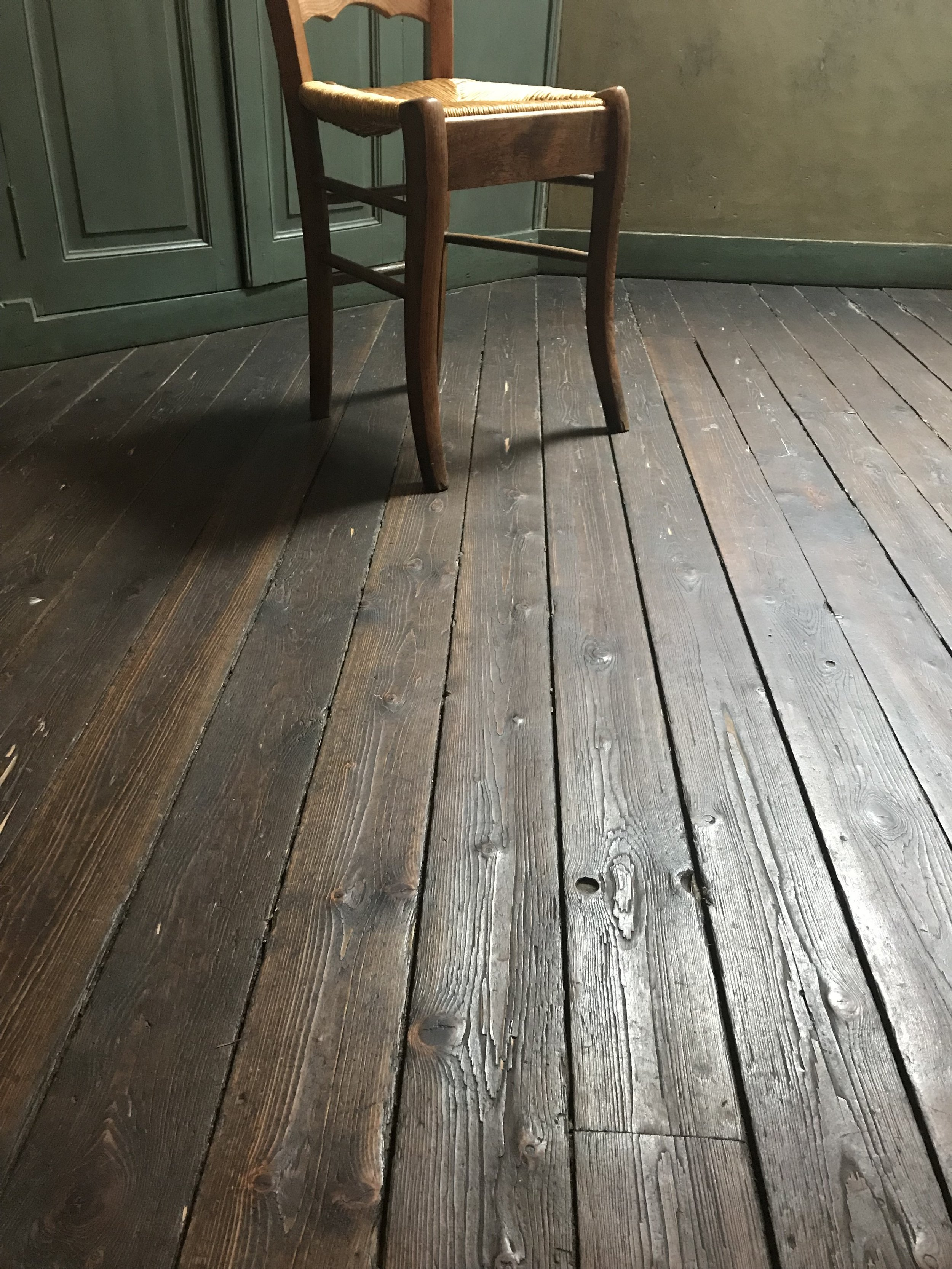 Sunlight warming the wooden floorboards in Van Gogh's room at the Auberge Ravoux