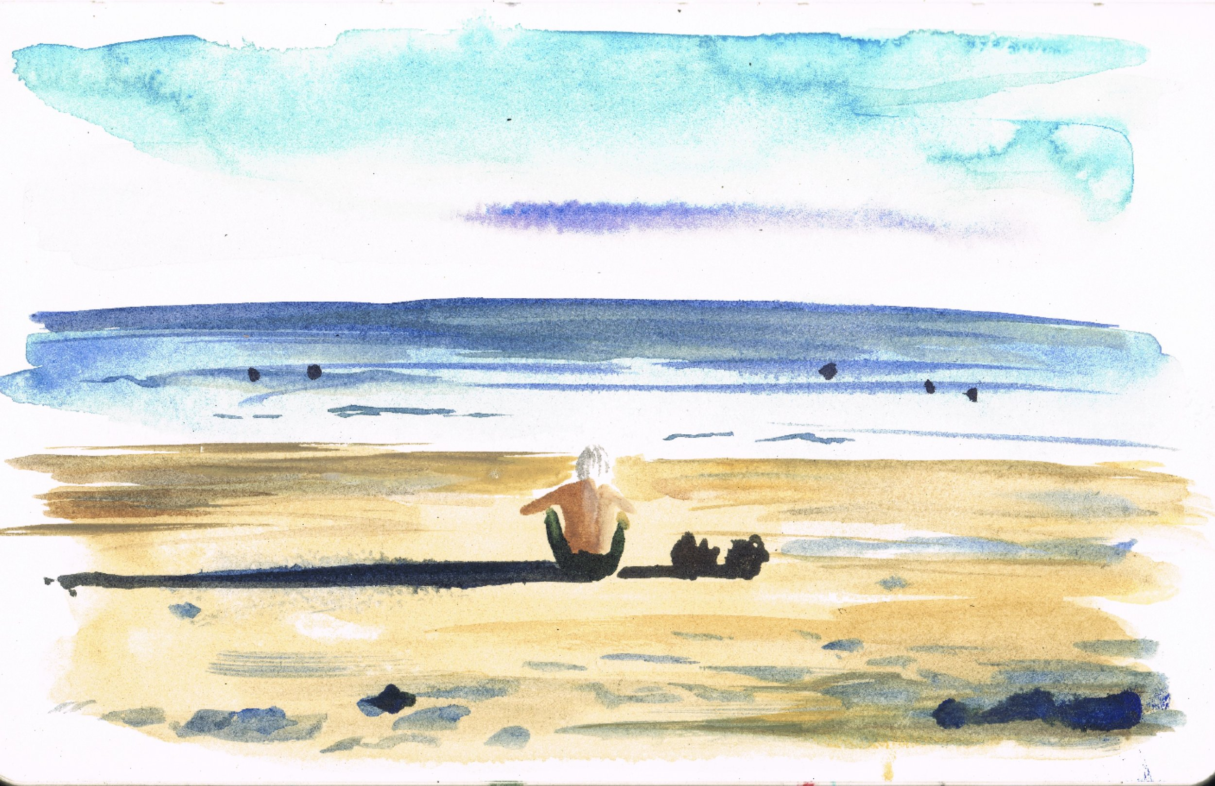 Man sat on Yuigahama beach looking out to sea