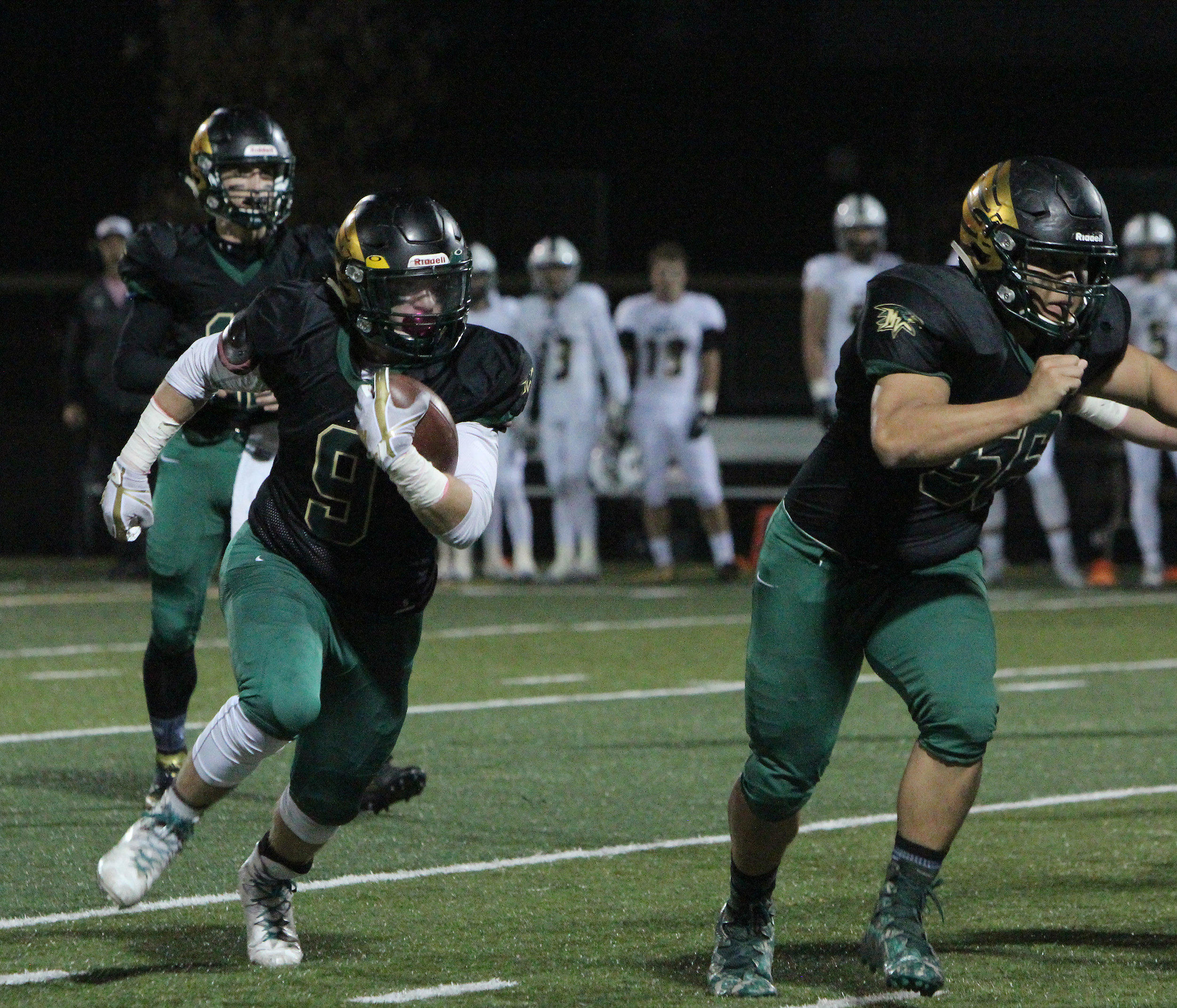 Senior Colton Whiteside craddles the ball after a handoff.