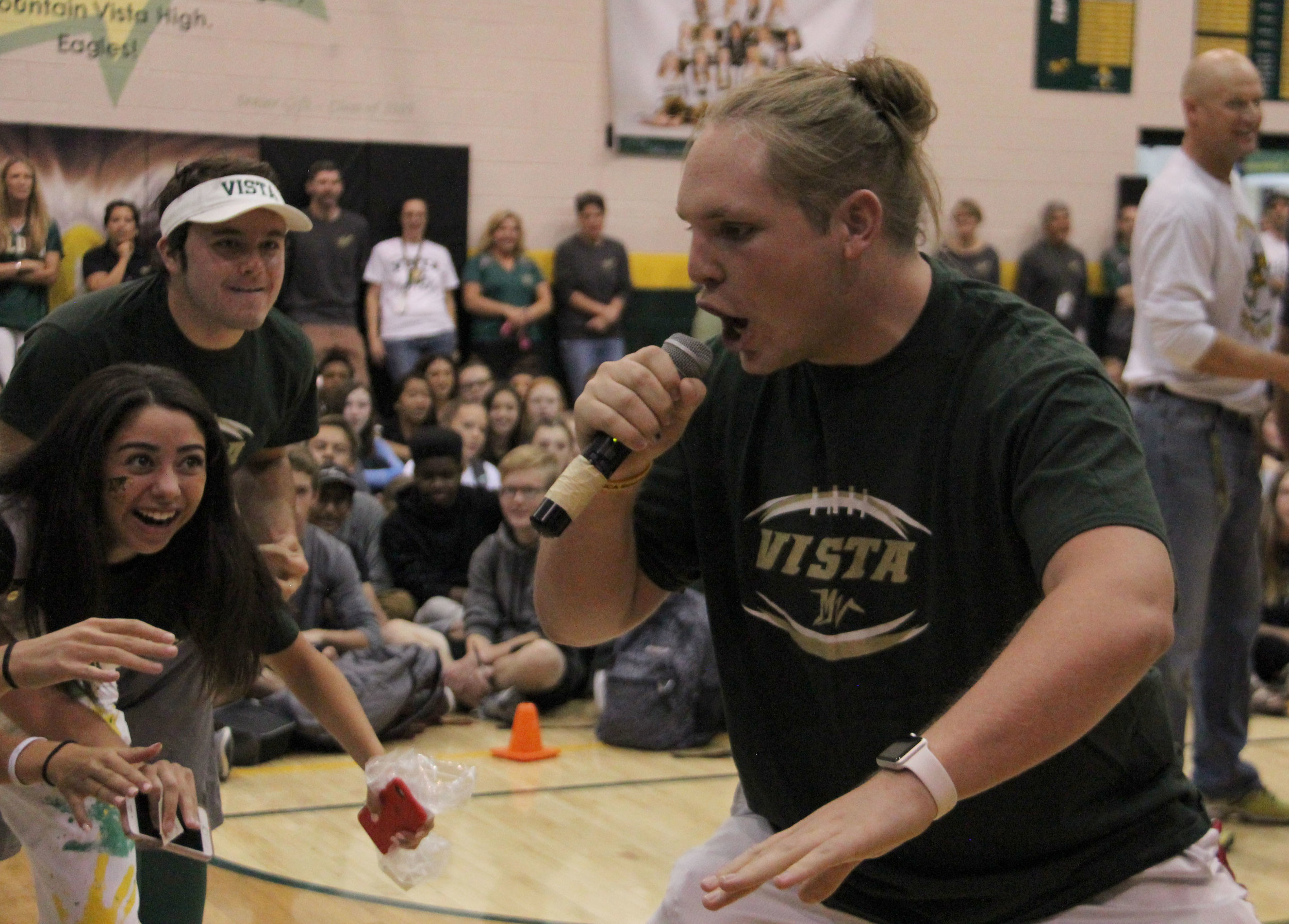 """Senior Chris Yockey competes in the """"Yea Boi"""" competition during the homecoming assembly with fellow seniors observing his performance."""