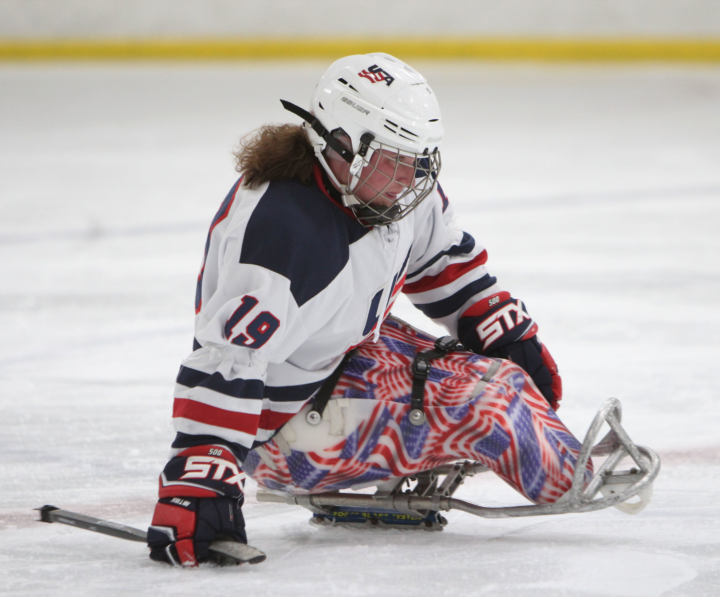 Kelli Anne Stallkamp, a USA Disabled Sled Hockey defender, skates towards the puck in a game against the Colorado Avalanche.
