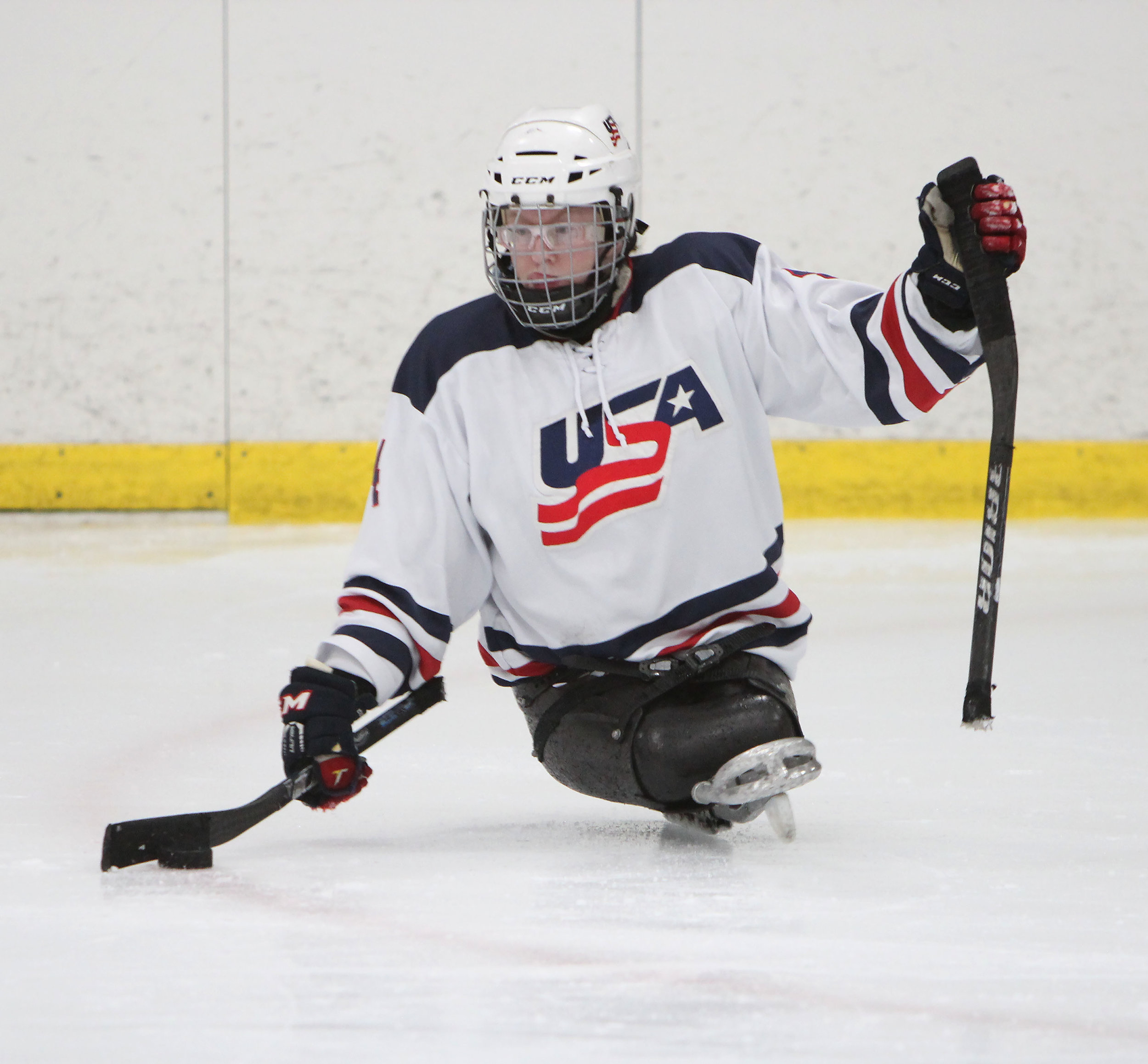 A U.S. Women's sled hockey forward grabs the puck before skating down towards the goal.
