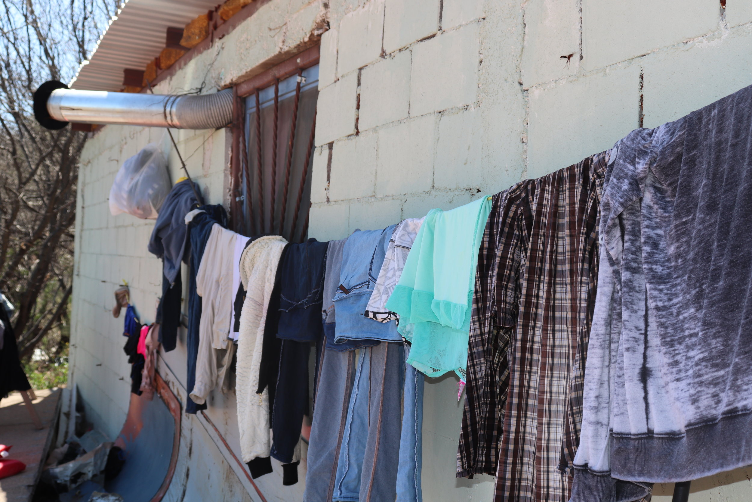 There are no washers or dryers at La Roca, so the migrants wash donated clothing in a sink and hang them to dry in the heat.