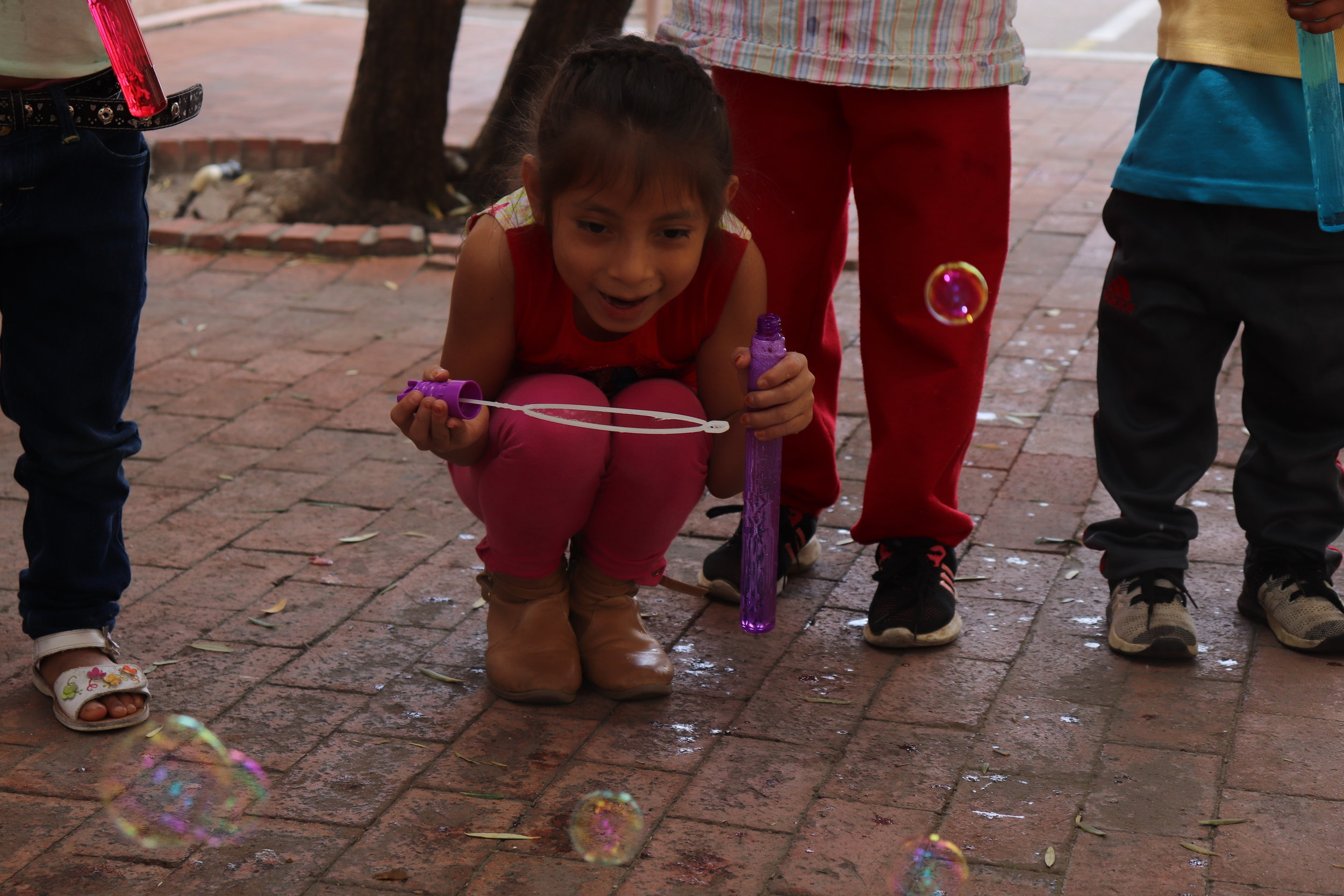 A young girl poses for a photo outside of The Inn Project after playing with the bubbles we donated. According to statistics provided by The Inn Project, 76% of the asylum seekers they have helped are from Guatemala.