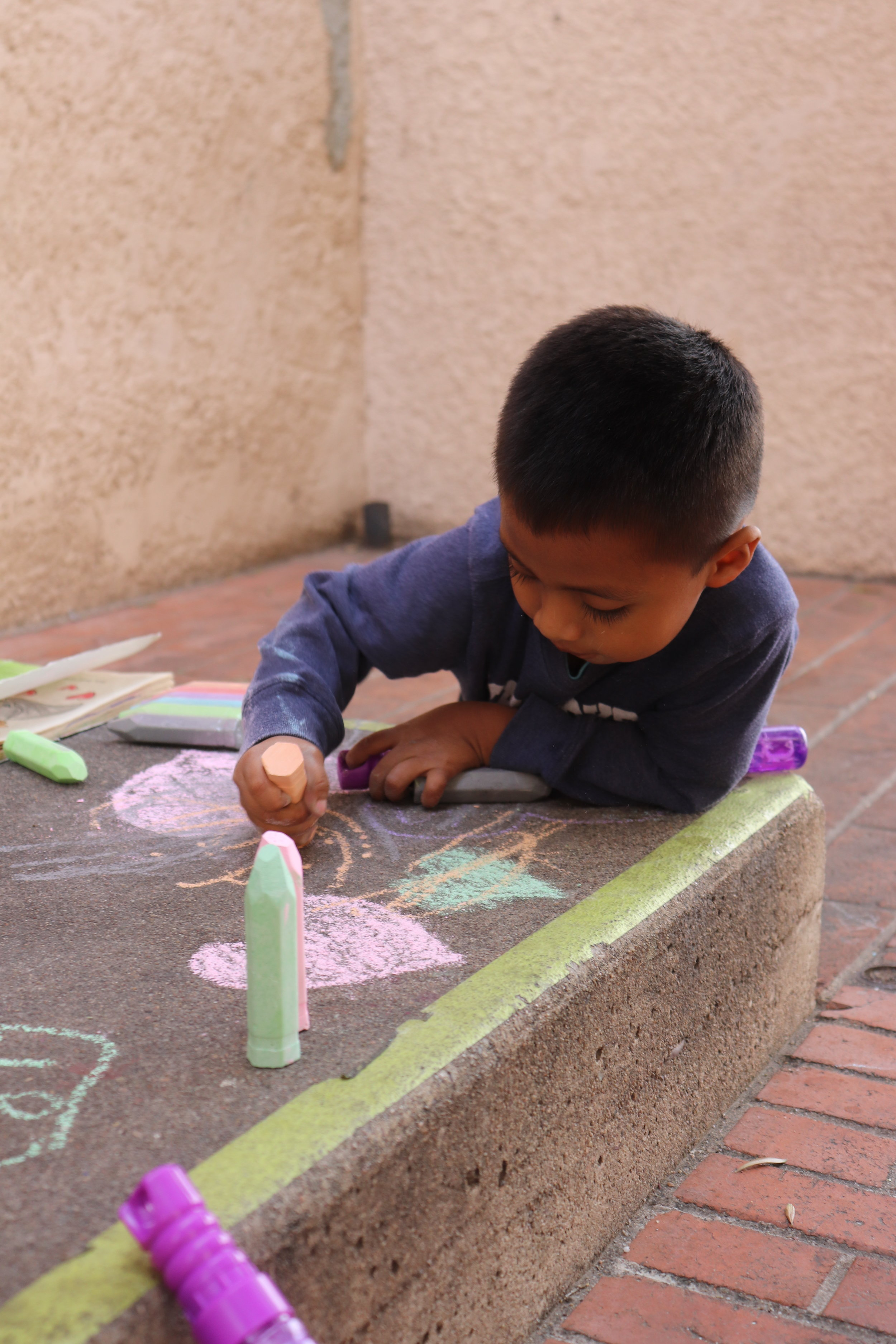 A young boy plays with the donated chalk on the steps of The Inn Project. His mother watched carefully from down the stairs where the shelter is located.