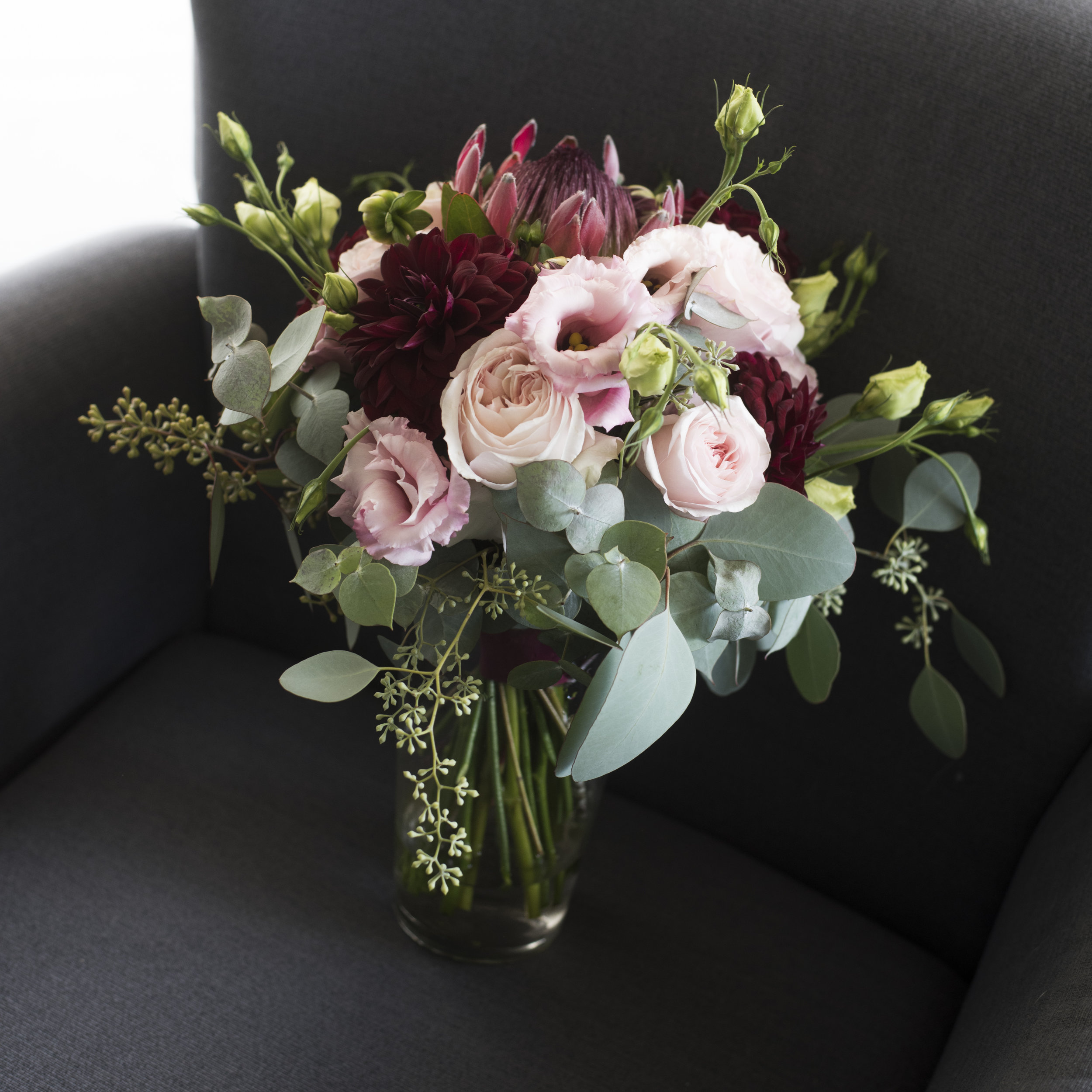 Blush David Austin roses, pink lisianthus, burgundy dahlia, pink protea and native foliage bound in burgundy ribbon.