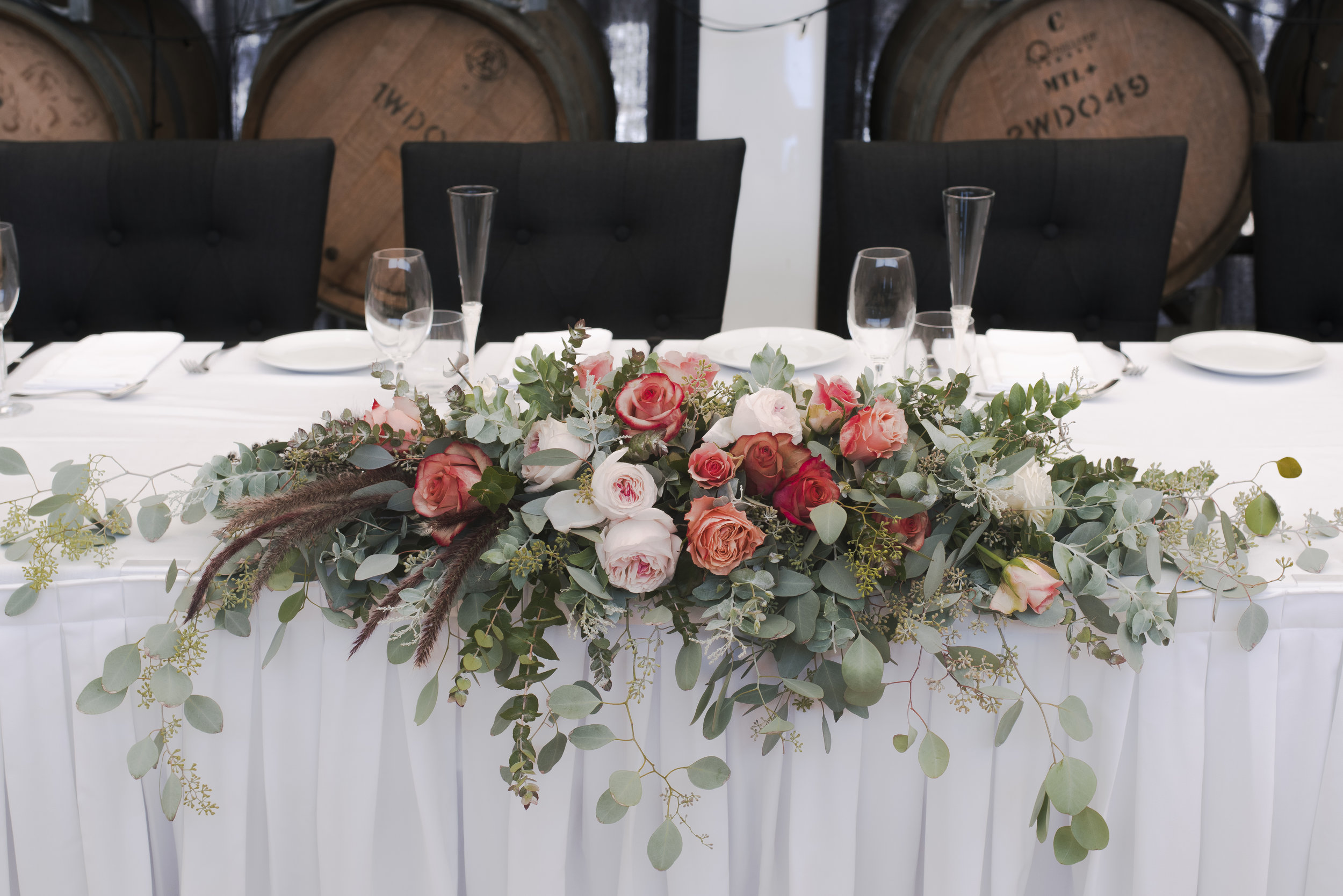 Contemporary style long and low table arrangement with blush David Austin roses, peach roses, native foliage and native grass.