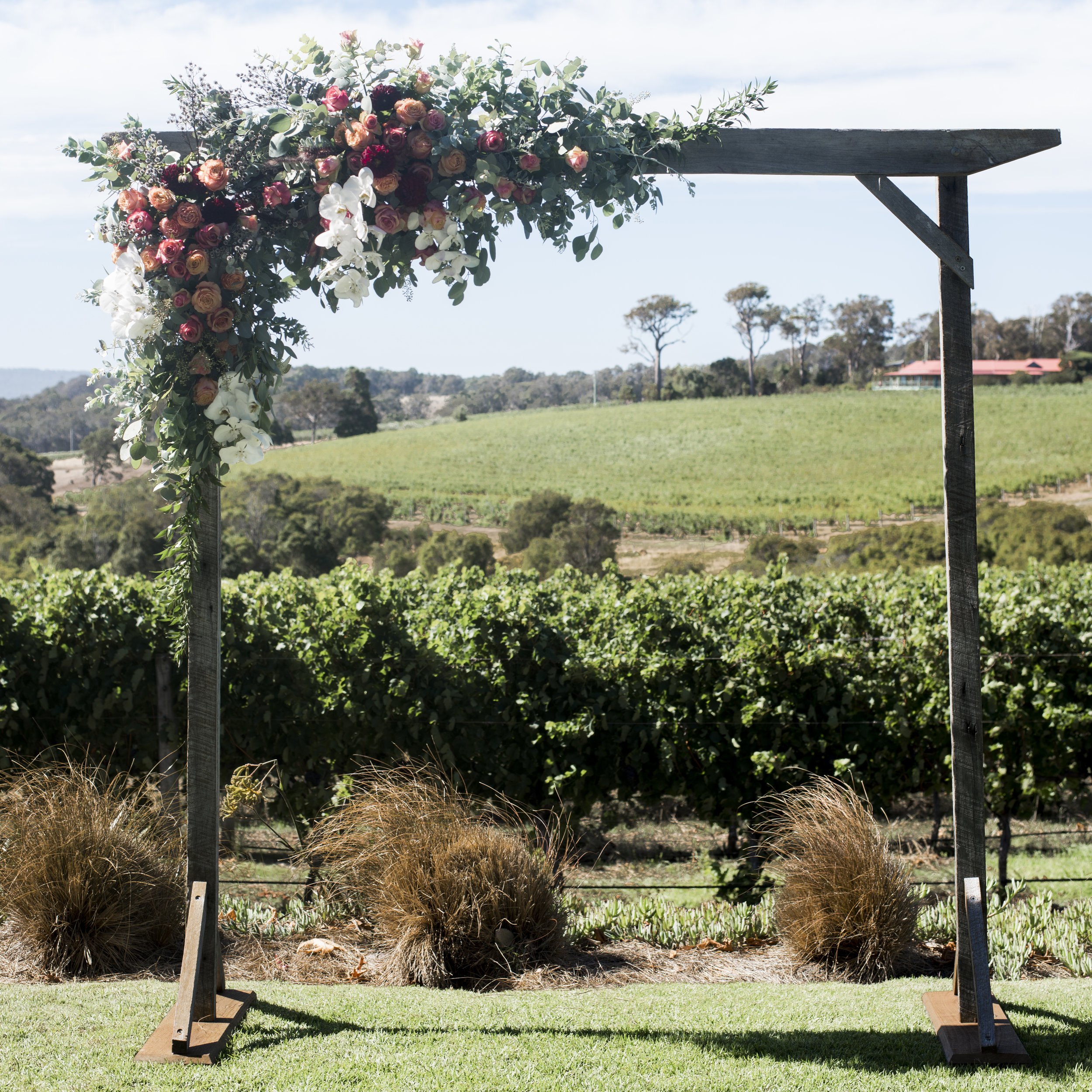 "Corner ""L"" shape arbour arrangement with white moth orchids, burgundy dahlias, strilingia, pink roses, peach roses and native foliages.  Wooden arbour from  Yallingup Event Hire   ."