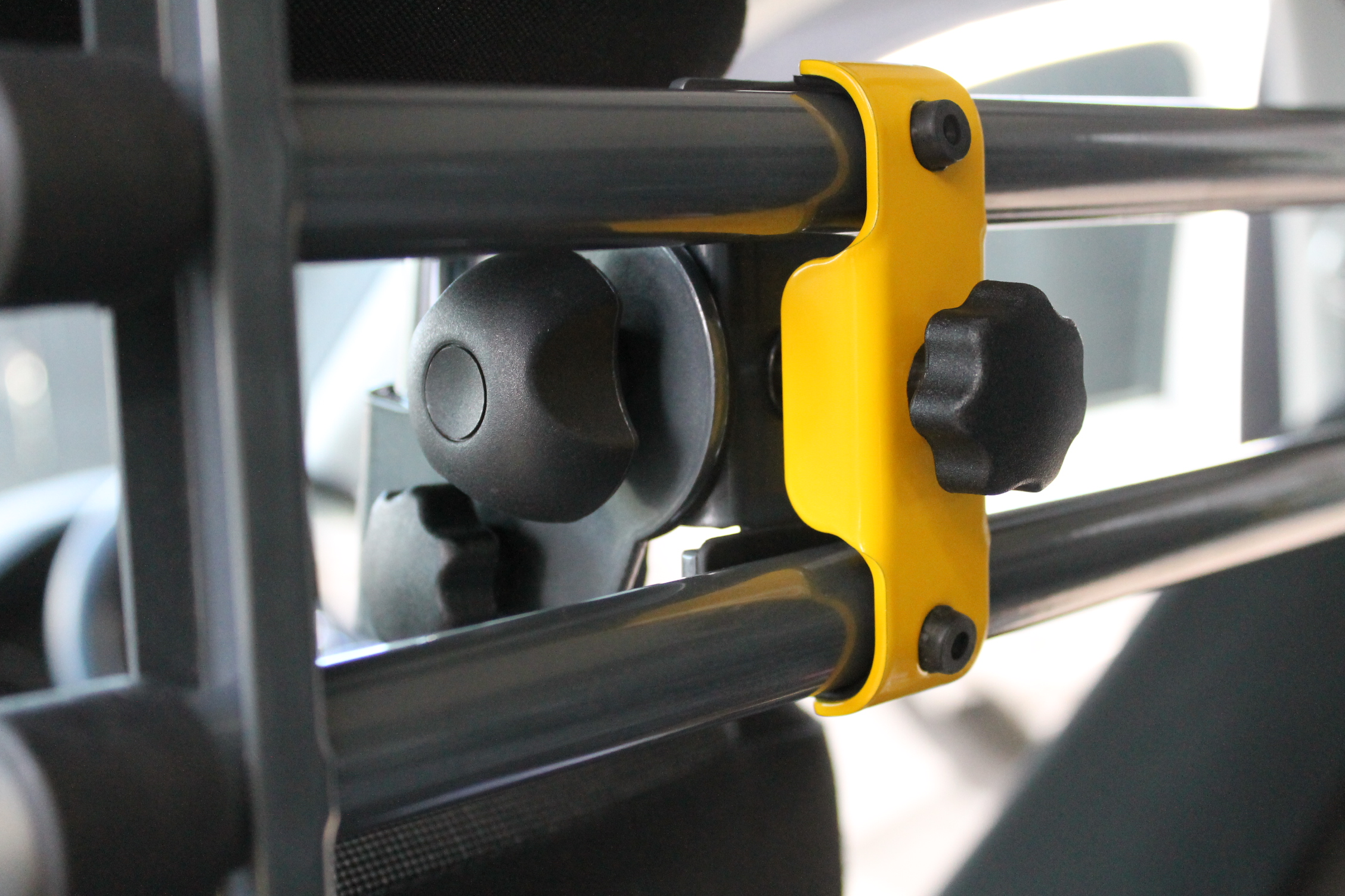 Yellow clamp attaches the bars to the attachment mechanism.