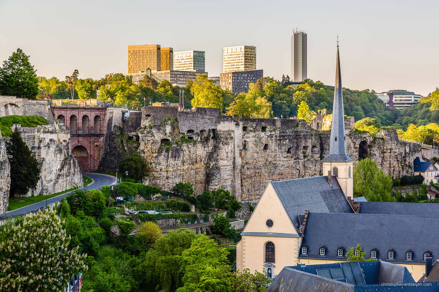 Summer in Luxembourg - Luxembourg City's Grund with the Abbey of Neumunster and the Casemates, as well as the skyscrapers of the Kirchberg in the background - Eras United