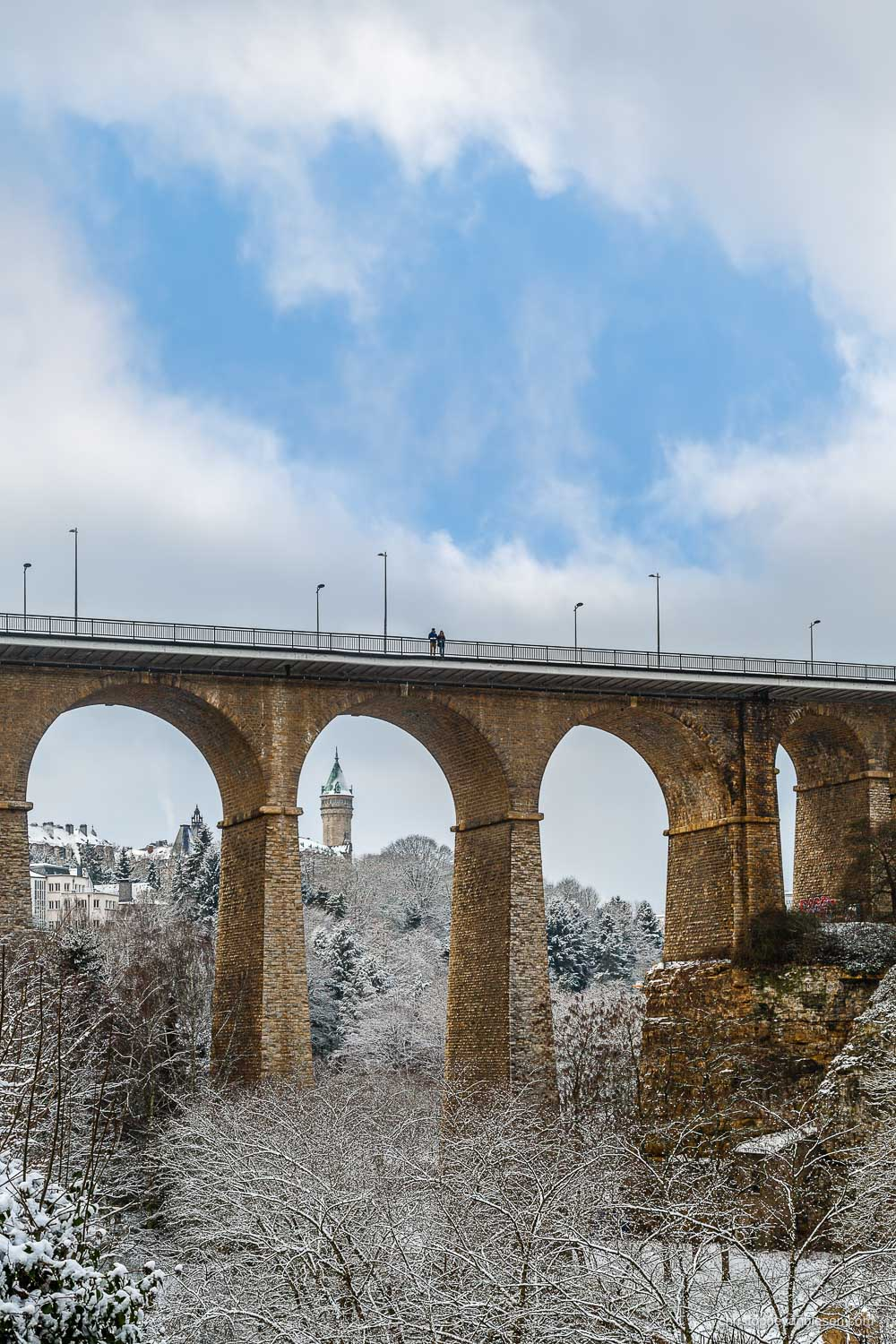 Winter in Luxembourg - The tower of the BCEE seen beneath the arches of the Passerelle during winter in Winter in Luxembourg - Cold Hands, Warm Hearts