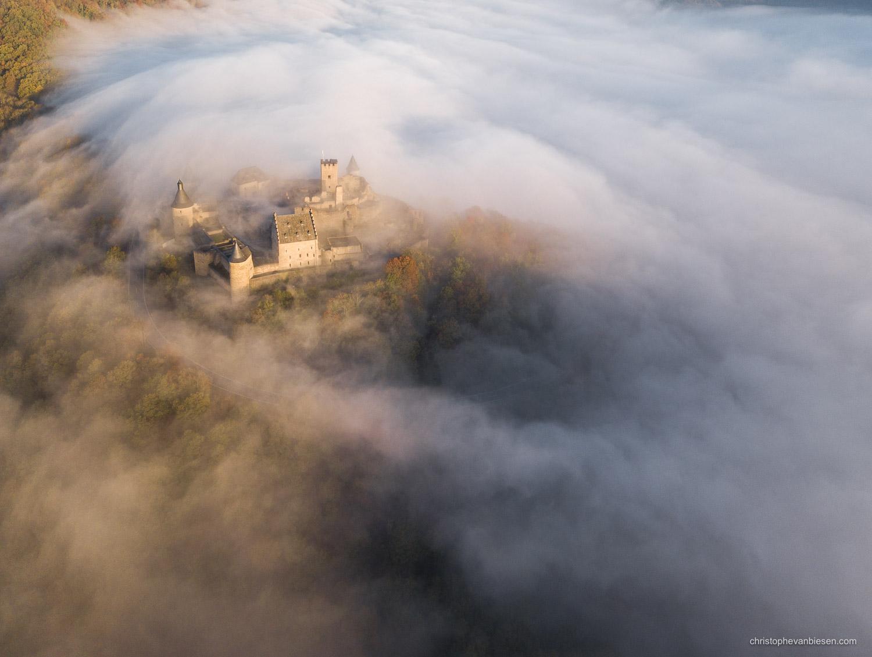 Bourscheid Castle in the fog - Chateau de Bourscheid - Luxembourg - Drone - Bourscheid Castle above a sea of fog seen from the air - Wave Breaker