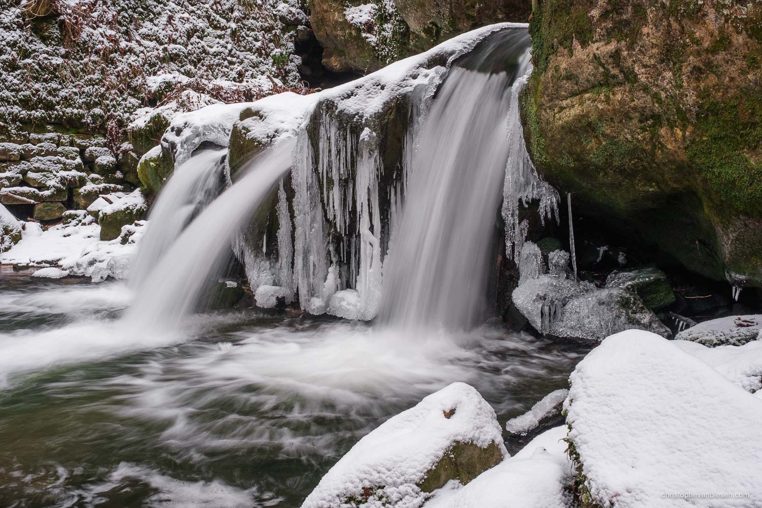 Visit the Mullerthal - Luxembourg - A cold winter has frozen parts of the Mullerthal's Schiessentumpel waterfall in northeastern Luxembourg - Frozen Waters