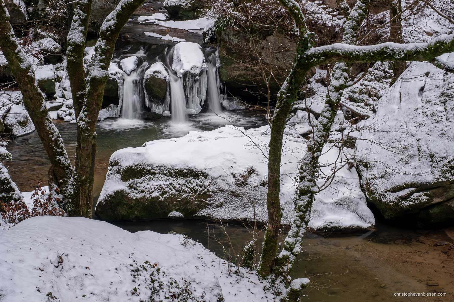 Visit the Mullerthal - Luxembourg - A cold winter has frozen parts of the Mullerthal's Schiessentumpel waterfall in northeastern Luxembourg - Winter's Grasp