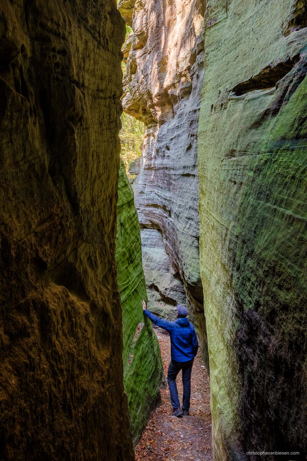 Visit the Mullerthal - Luxembourg - Explorer hiking in the narrow canyons of the Mullerthal region in Luxembourg - Exploring the Mullerthal