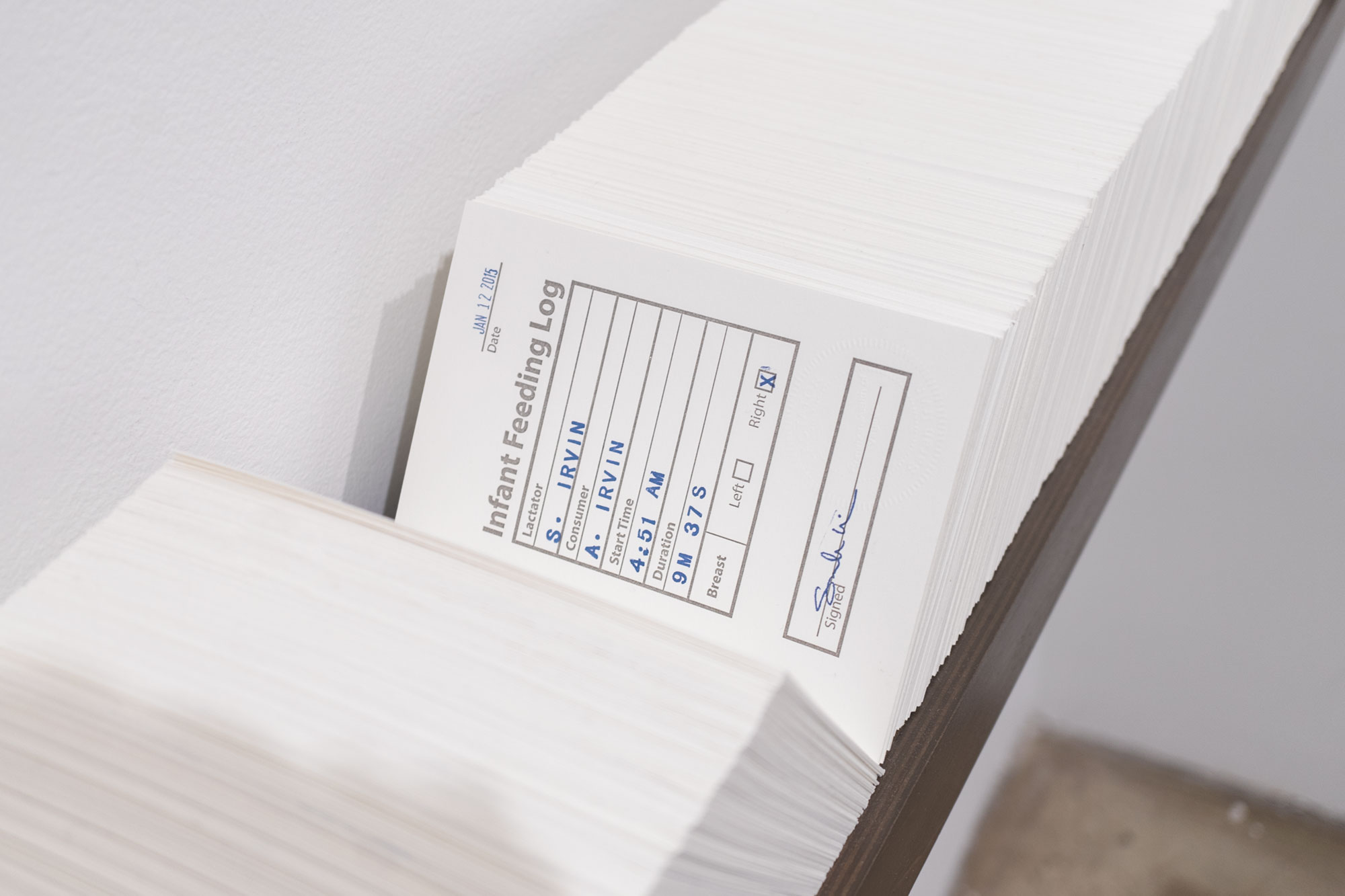 Sarah Irvin, Infant Feeding Log, 2018, Card catalogue with 2,435 unique forms, hand-set letterpress colophon & title page, metal rods, wooden base w/ milk paint, 7 x 78 1/4 inches