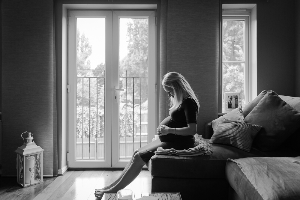 Expecting mother looking at her baby bump on a couch near a large window during a newborn photo session in black and white