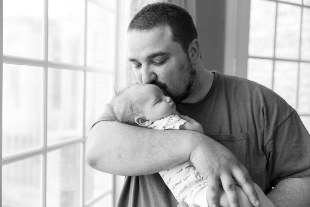 Father holding and kissing newborn daughter on forehead near a large window during newborn photo session in black and white