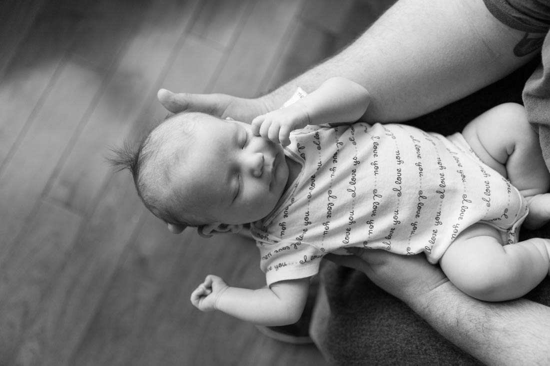 Newborn baby girl sleeping in her father's arms during a newborn in home session