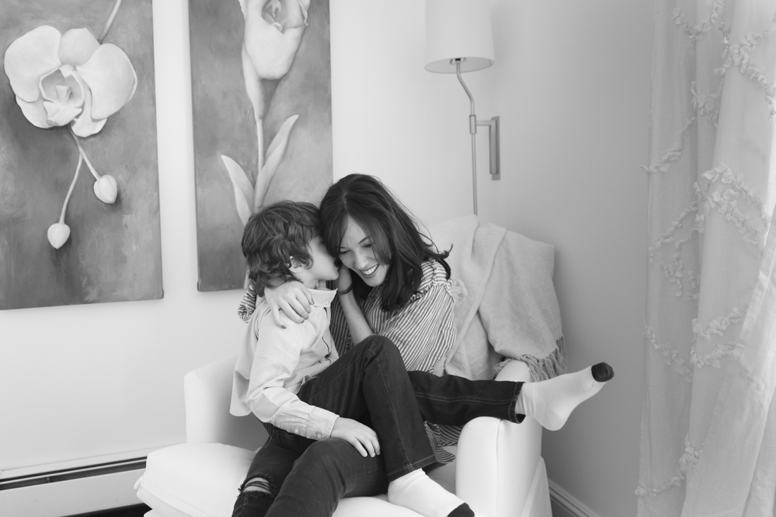 NYC FAMILY PHOTOgrapher - Mother hugging son on a corner chair in the bedroom