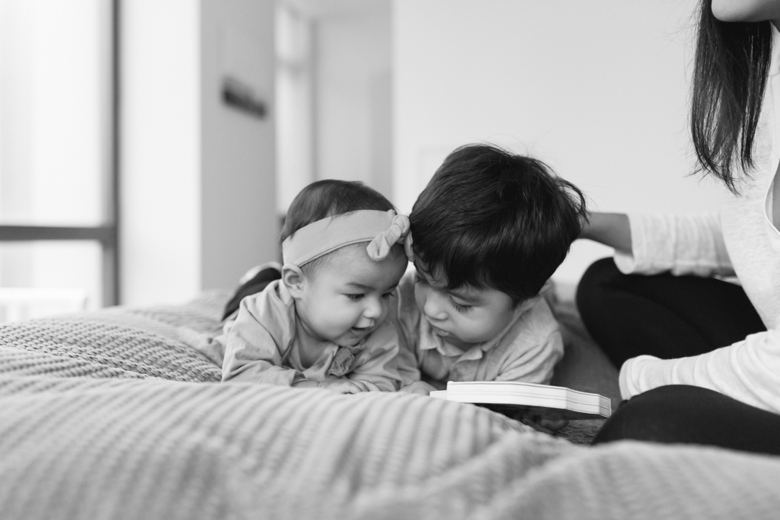 Siblings reading a book together on parents bed during a manhattan family session at home