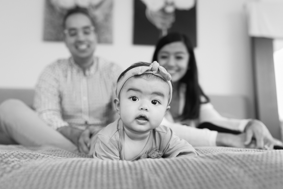 7 months old girl with her parents on bed during a family session in Manhattan