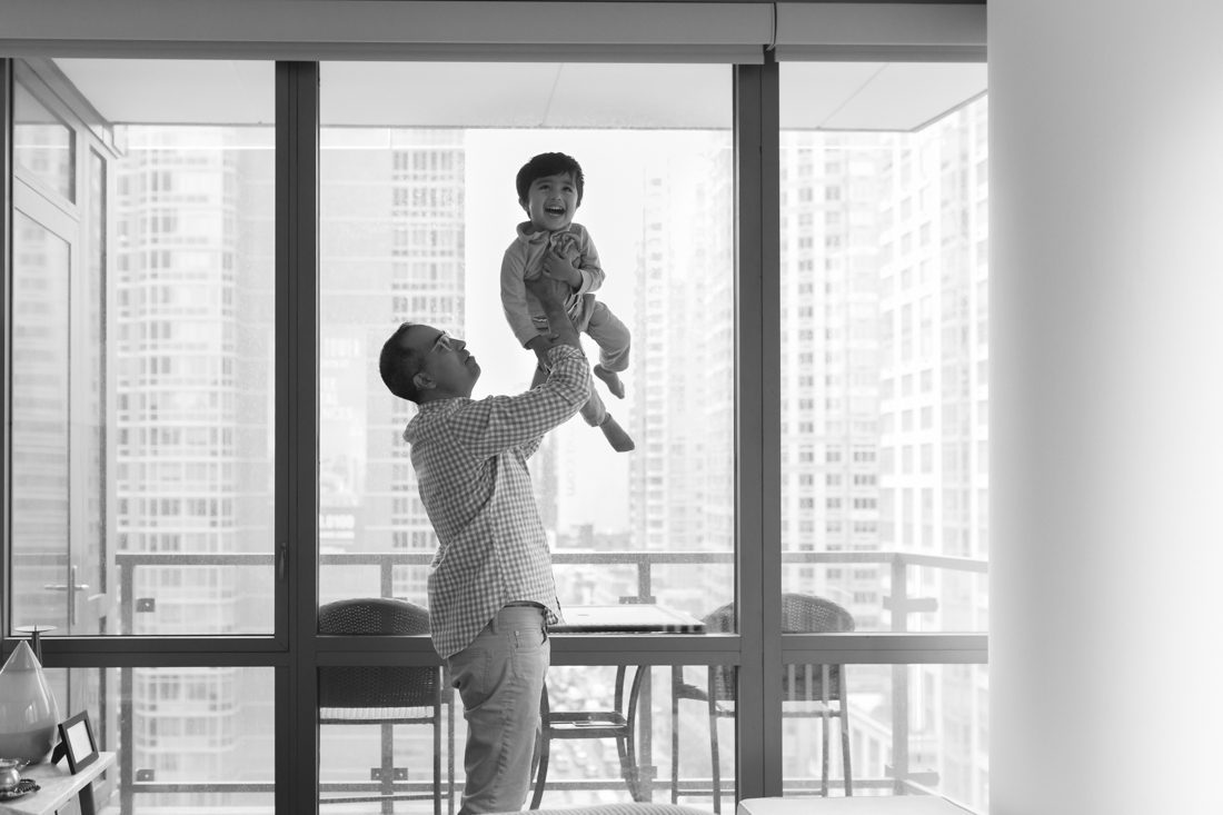 Dad playing helicopter with son during a New York Family photography session at home