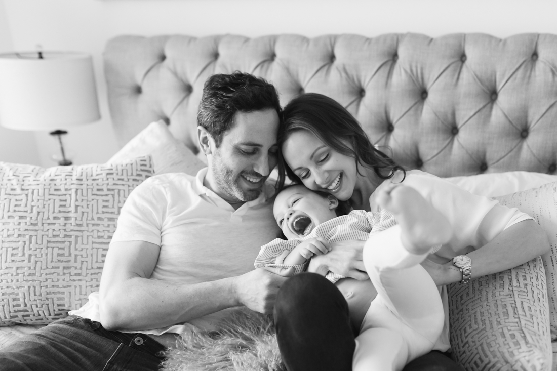 Parents hugging and laughing with toddler on bed during an in-home family session