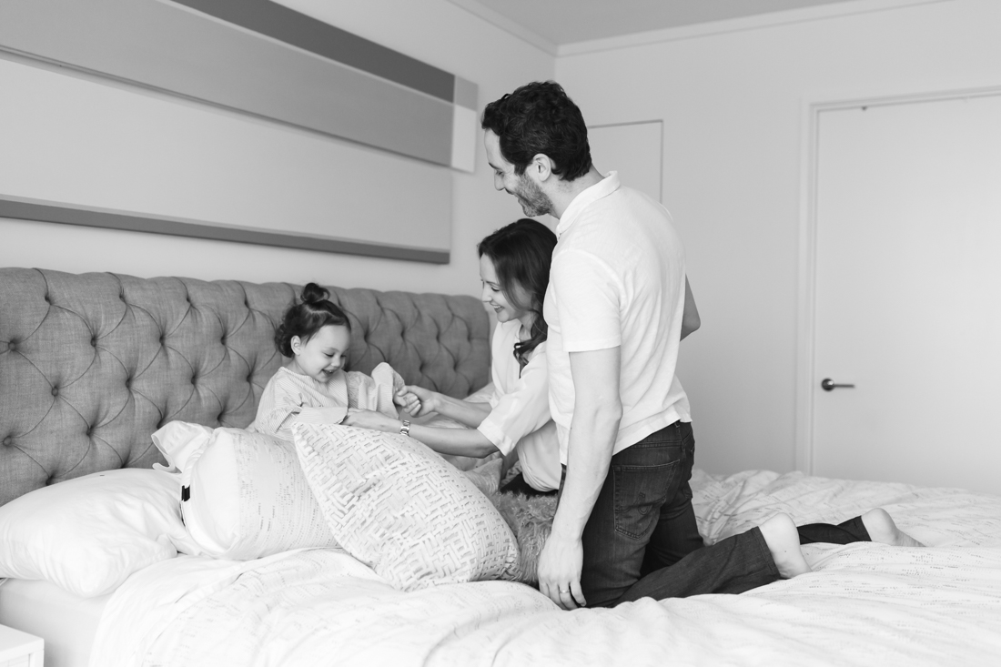 Parents and toddler playing in bed during in home photo session