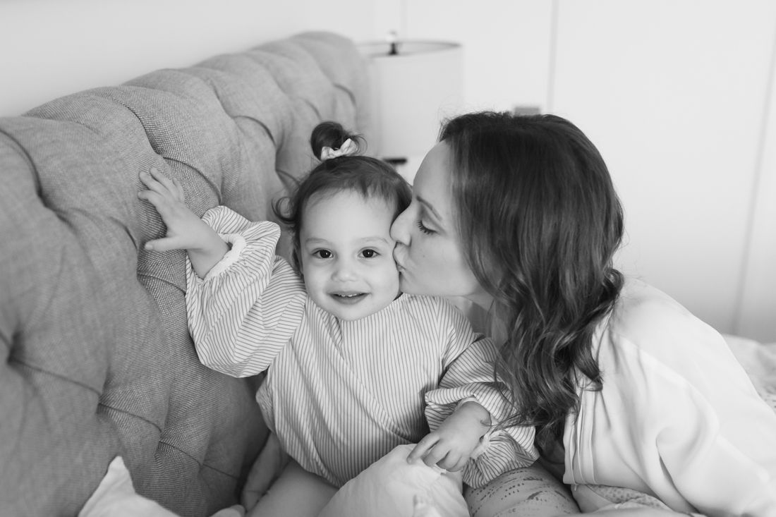 Mum kissing baby girl during in home session