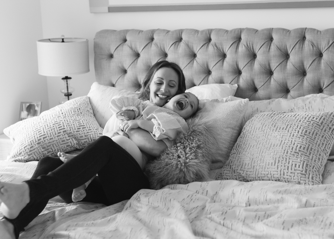 Mother and two years old daughter laughing on bed during a photo session at home