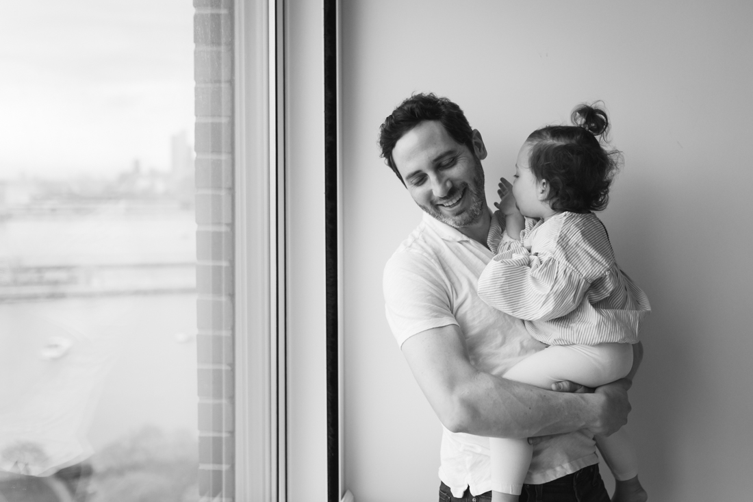 Father and daughter hugging and laughing during in home session