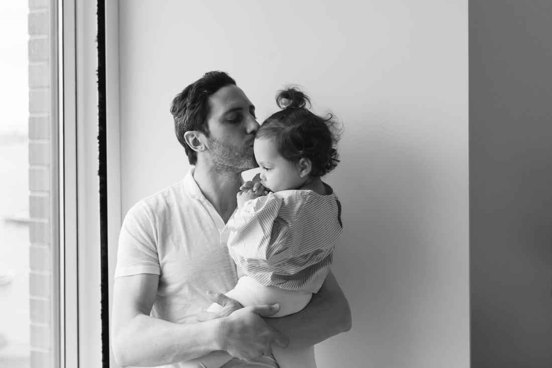 Father giving a kiss to his daughter during in home session