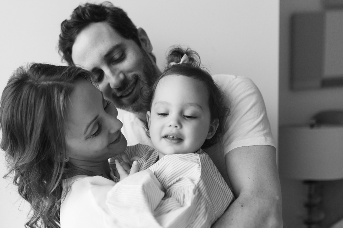 Family of three hugging during an in home family session