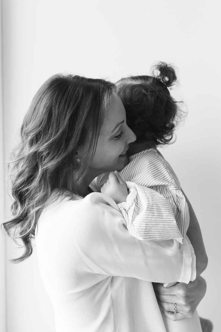 Mother hugging two years old daughter during in-home session