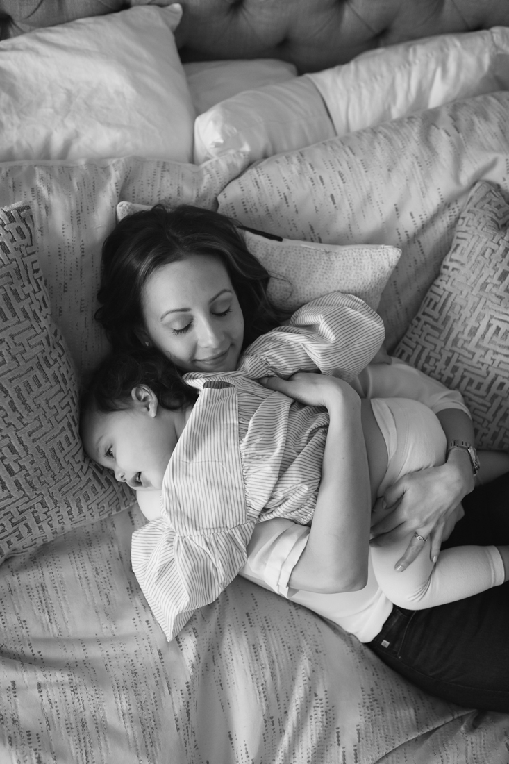 Mother and toddler girl hugging in bed