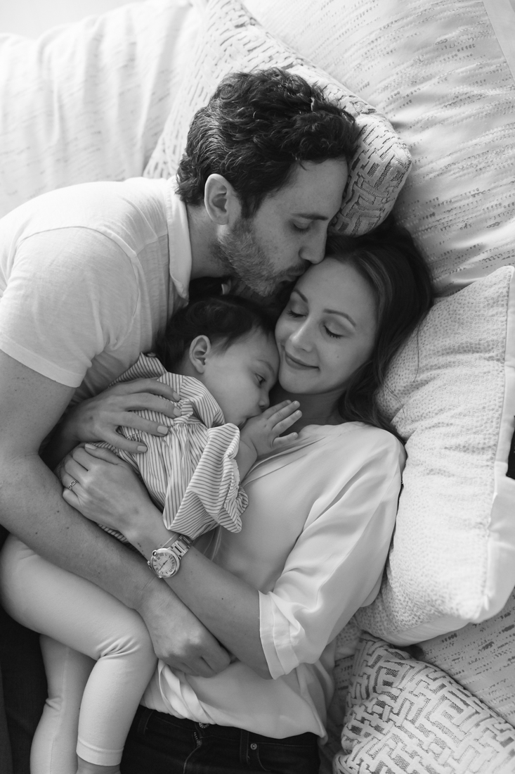 Parents hugging toddler on bed during an in-home family session