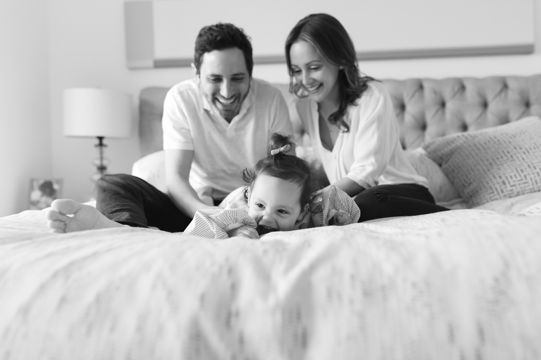 Parents hugging and playing with toddler on bed during an in-home family session
