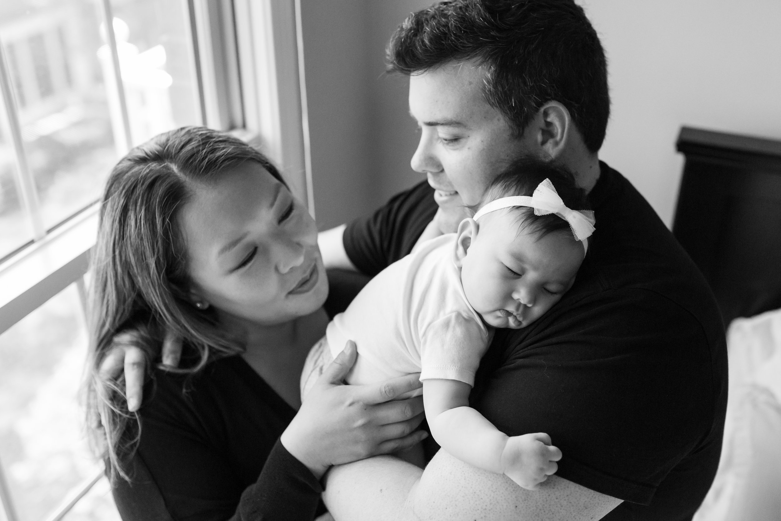 Black and white photograph of new parents holding their 4 months old daughter during an at home family session in NJ