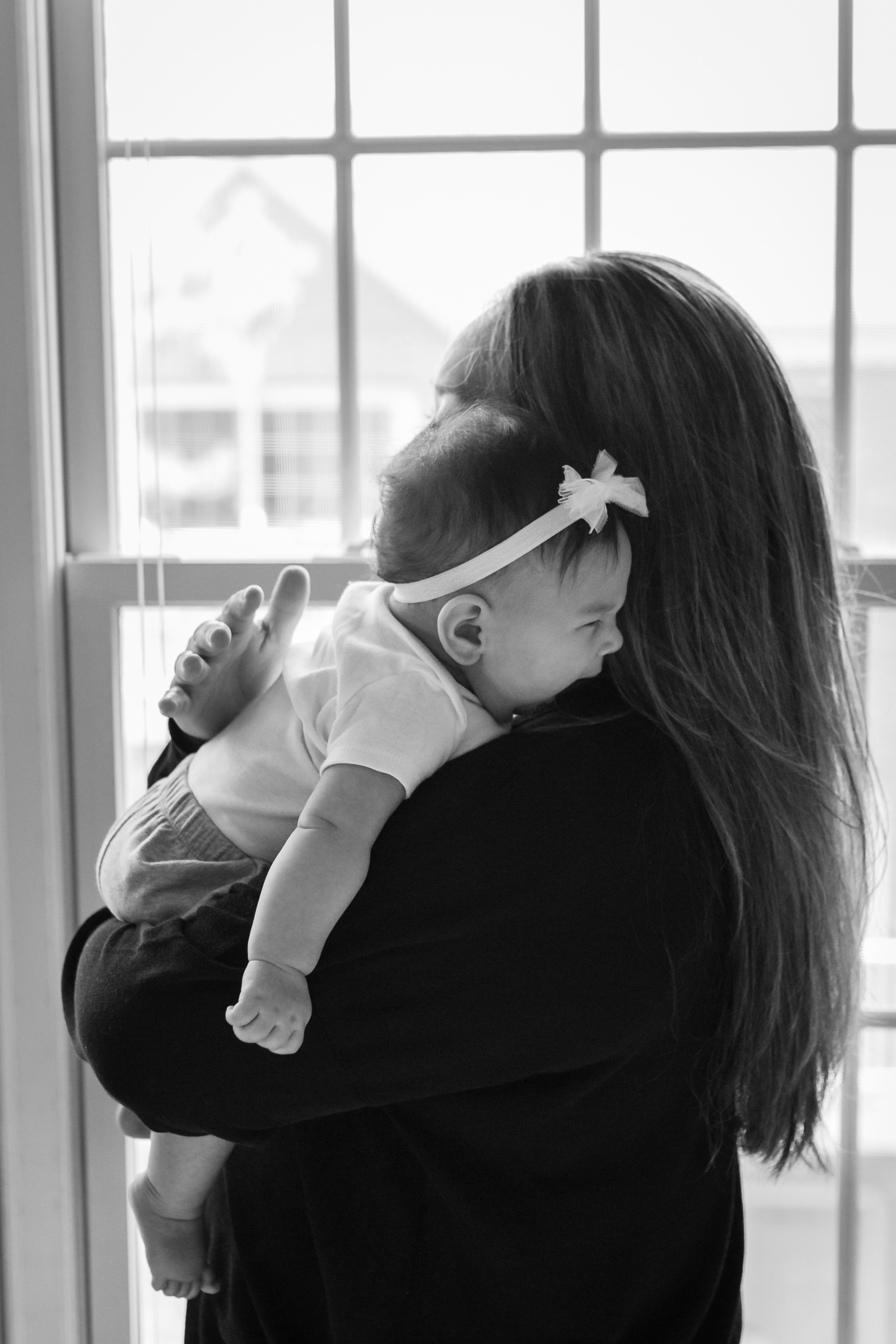Black and white photograph of new mom holding her 4 months old daughter during an at home family session in NJ