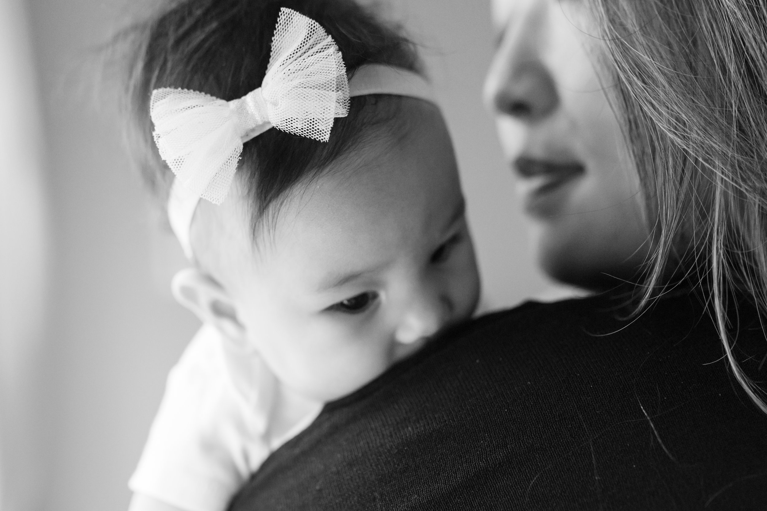 Black and white photograph of 4 months old baby girl in her mother's arms during an at home family session in NJ