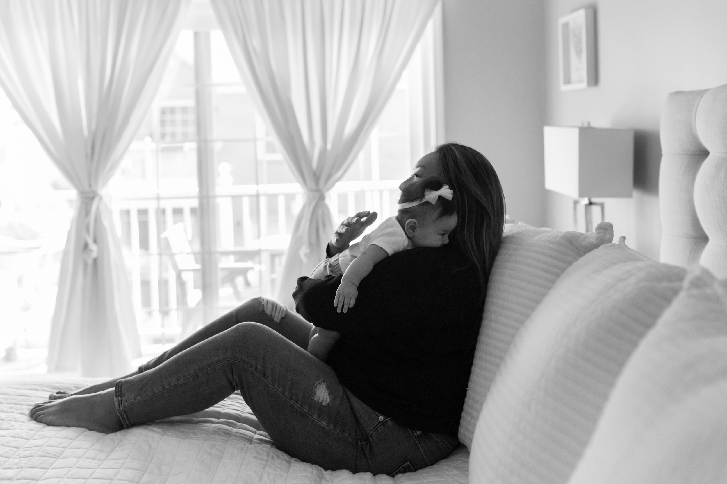 Black and white photograph of new mother holding her 4 months old daughter during an at home family session in NJ