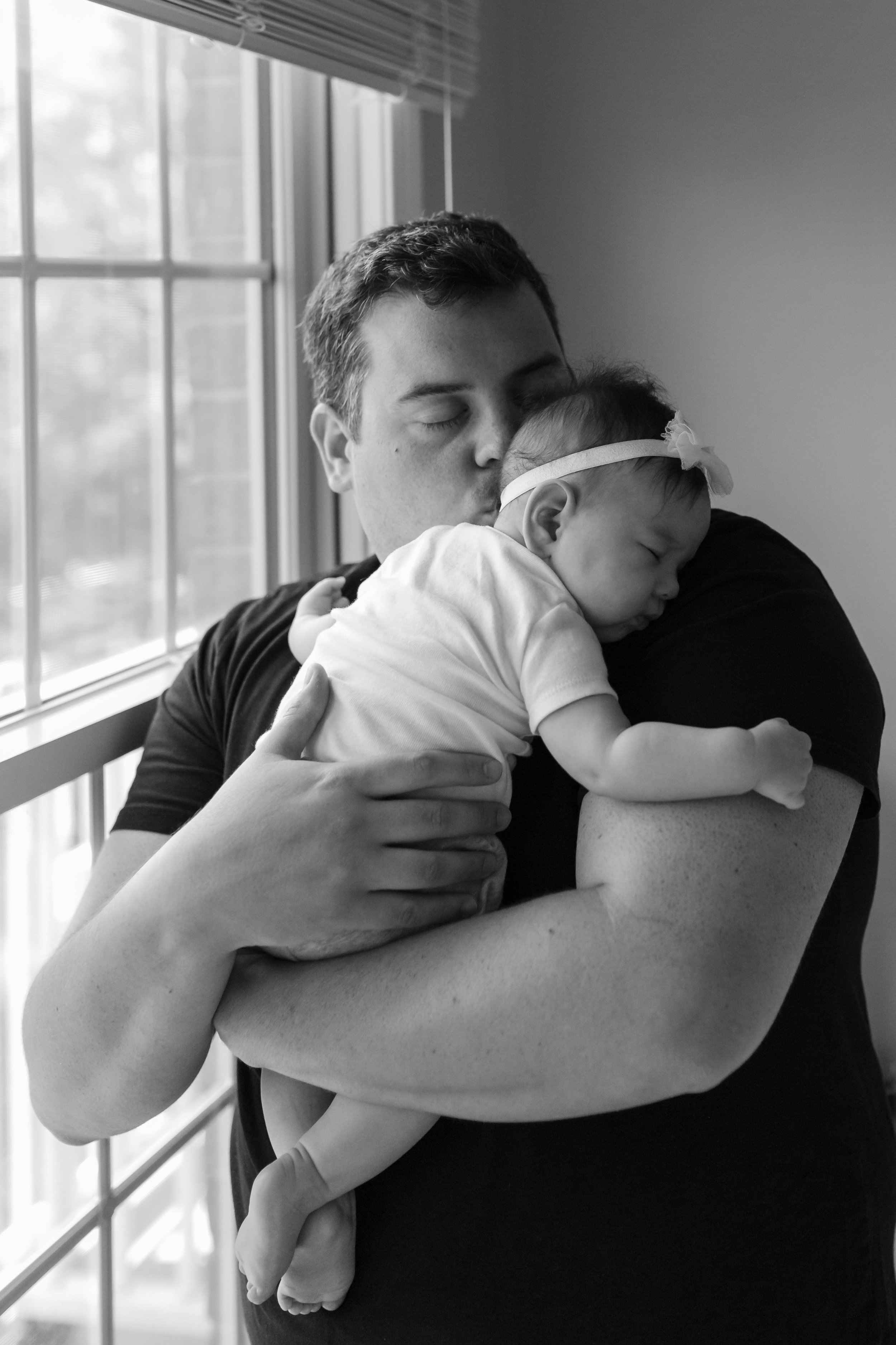 Black and white photograph of new dad holding his 4 months old daughter during an at home family session in NJ