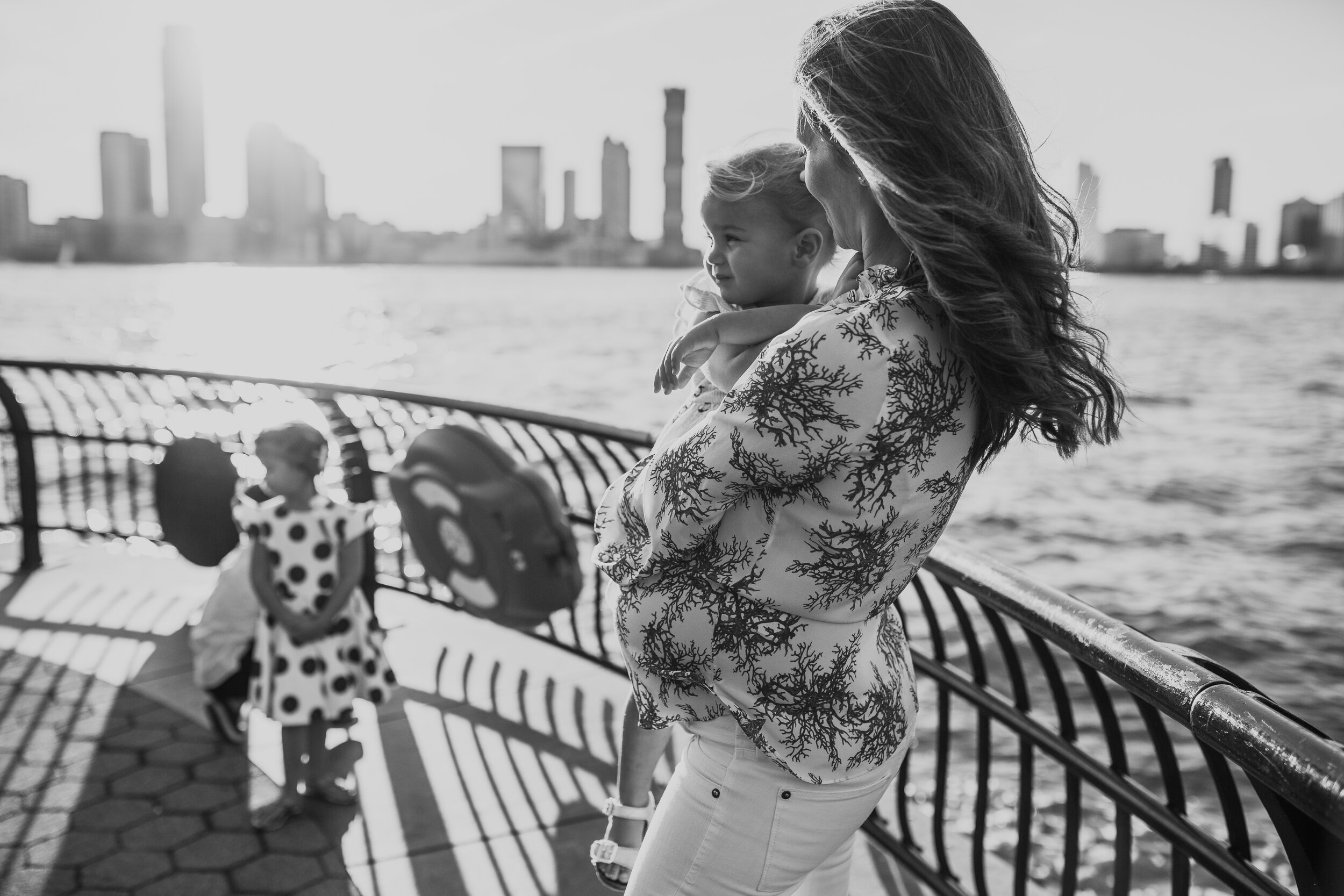 Expecting mother with her three children looking at the water during a maternity photography session in Manhattan