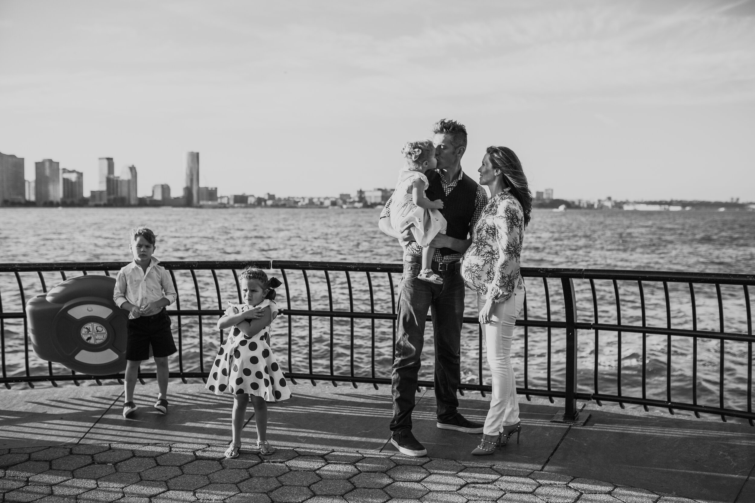 Black and white portrait of a family of five expecting their fourth child near the water in battery park city during a maternity and family photo session