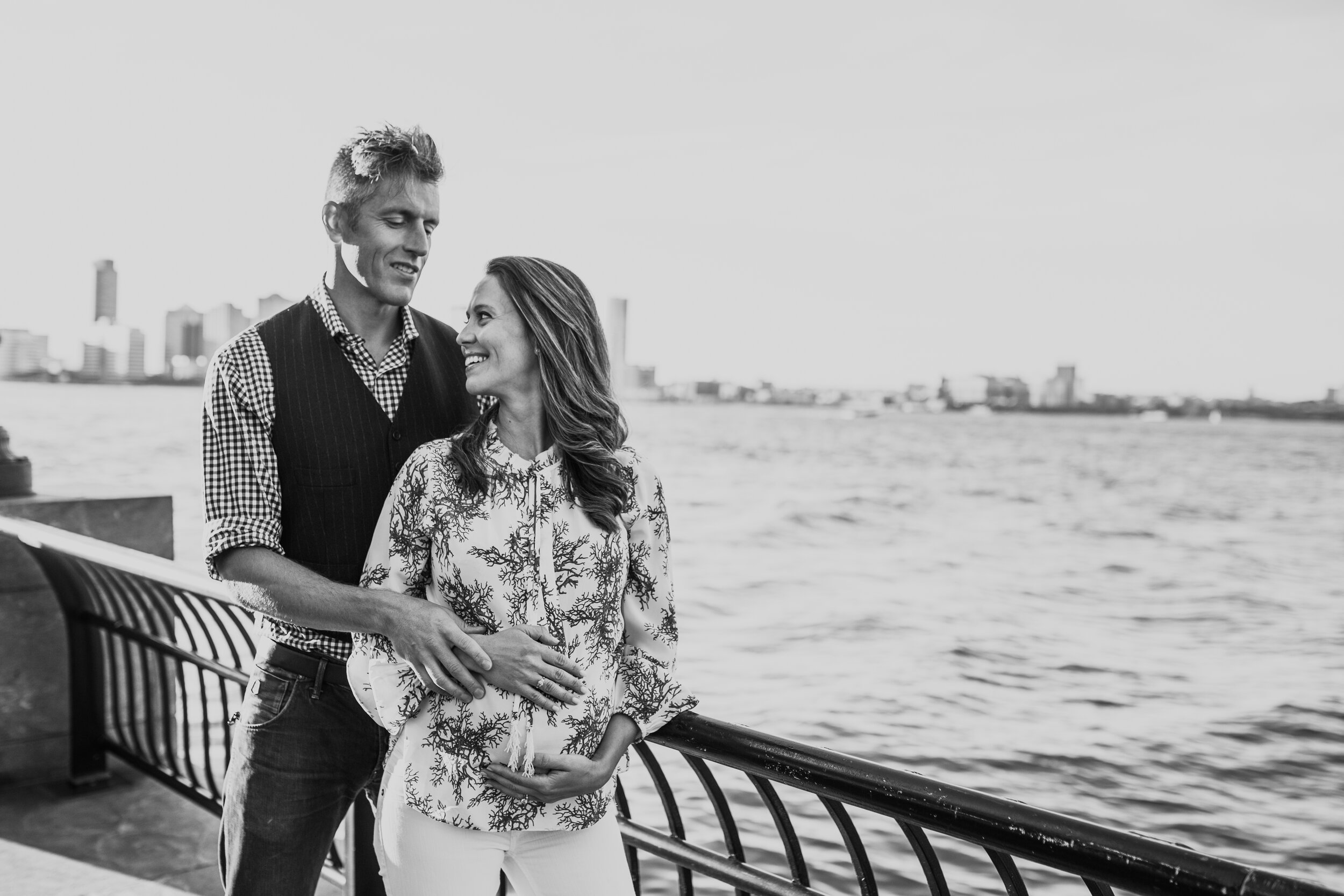 Expecting couple hands on belly holding each other near the water at Battery park city NY during a maternity photography session