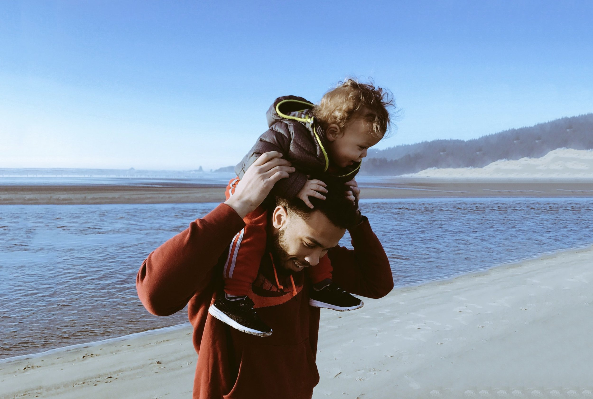 father with son on shoulders at beach.jpeg