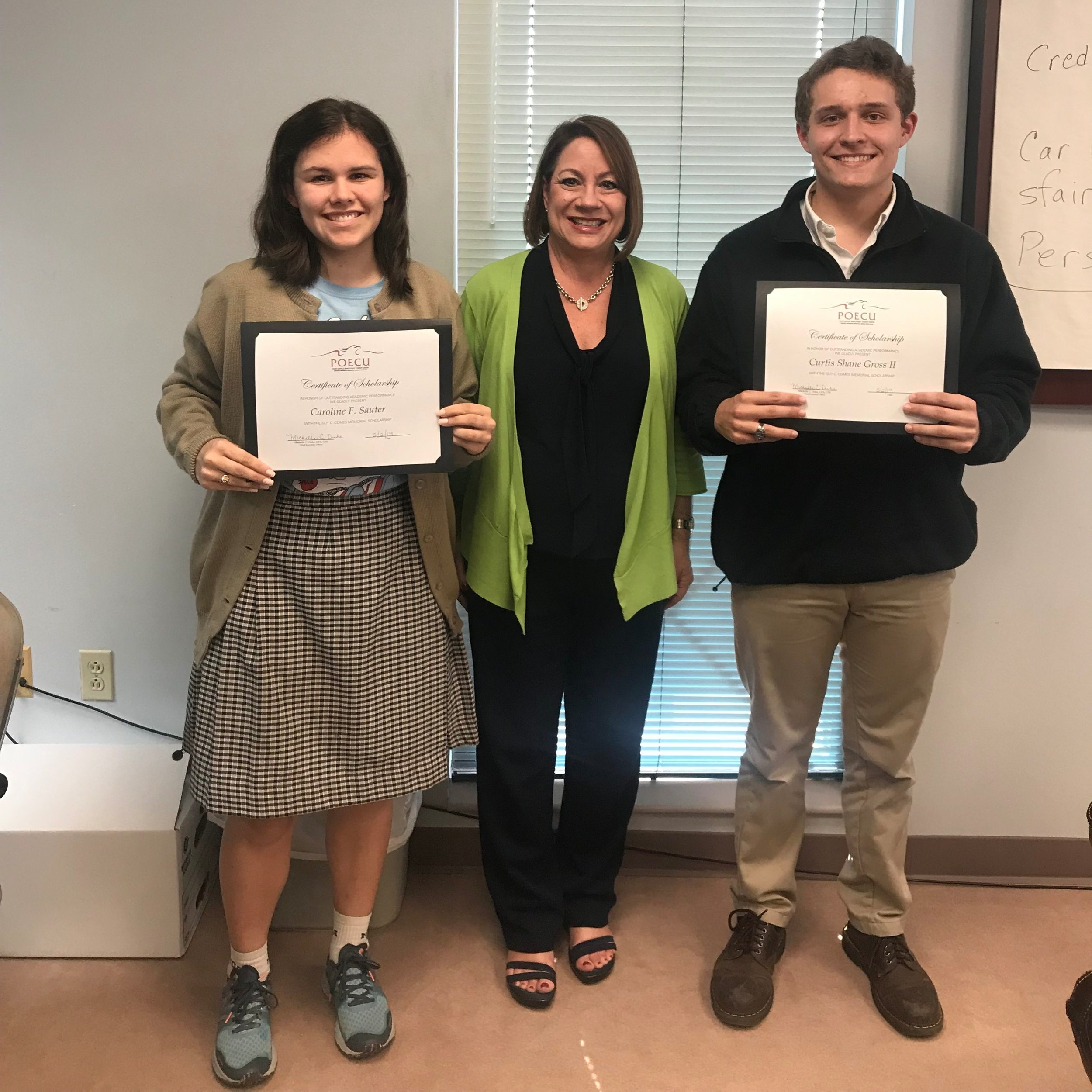 POECU CEO Michelle Duhe (center) presents Caroline Sauter (left) and Shane Gross (right) with the 2019 Guy C. Comes Scholarship.
