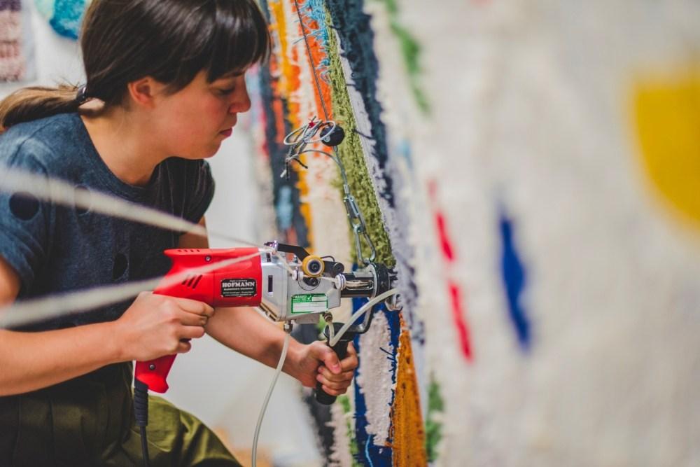 Katie Schwab using a hand-held 'carpet drill' type machine to 'handtuft.