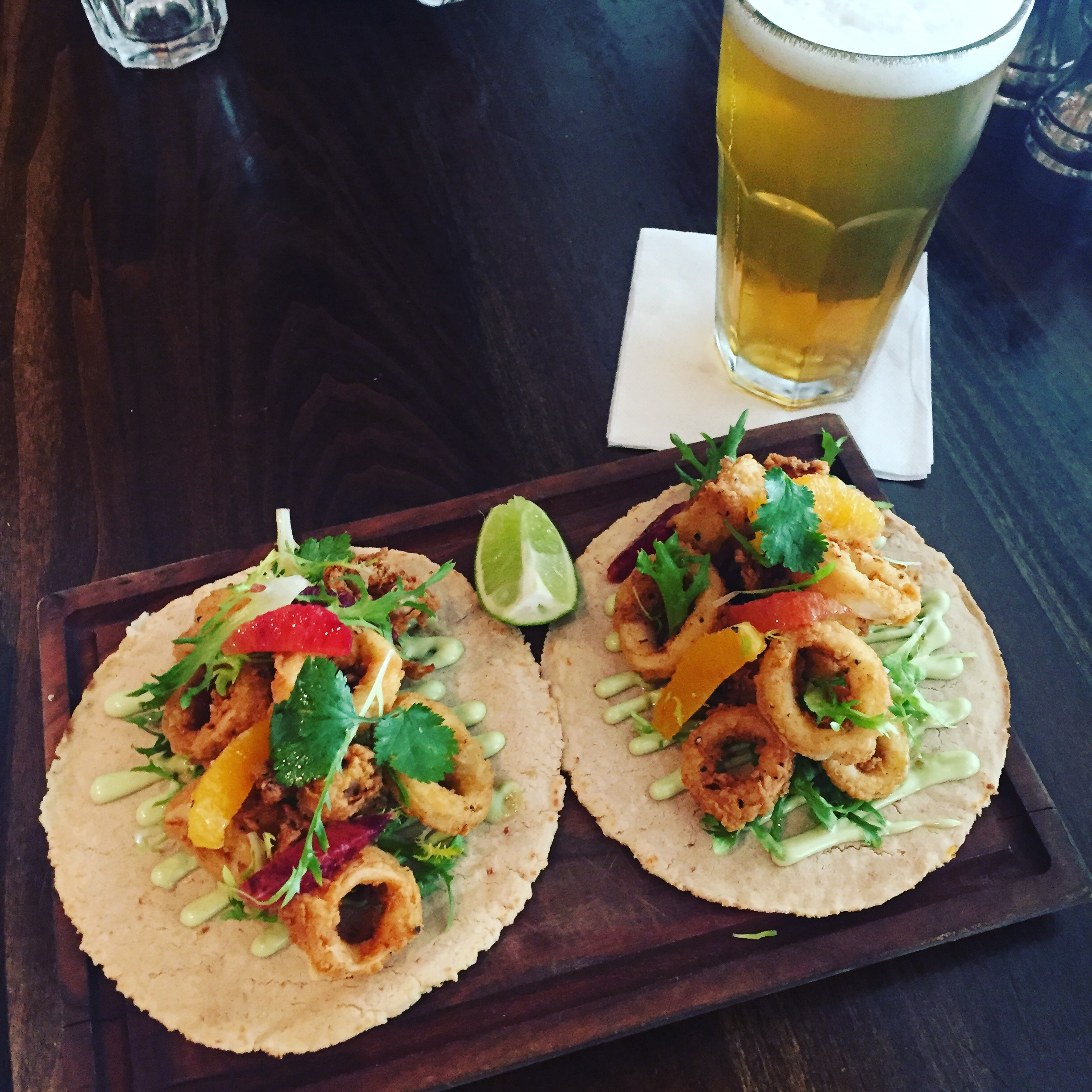 Crispy Calamari Tacos - Blood orange infused house made tortillas with lemon basil aioli, a citrus salad with frisee, cilantro leaves, blood and navel orange segments and lemon agrumato over crispy calamari.